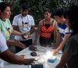 DESCRIÇÃO: Seis pessoas aparecem em torno de mesa onde estão sendo montadas pequenas placas de energia fotovotaica durante o curso. Uma lâmpada está acesa com a energia gerada pelo sol. Foto: Inês Campelo/MZ Conteúdo